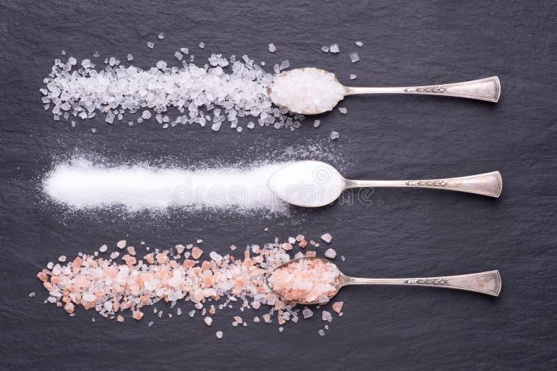 Divers genres de sel dans des cuillères d'argent sur le fond en pierre noir image stock