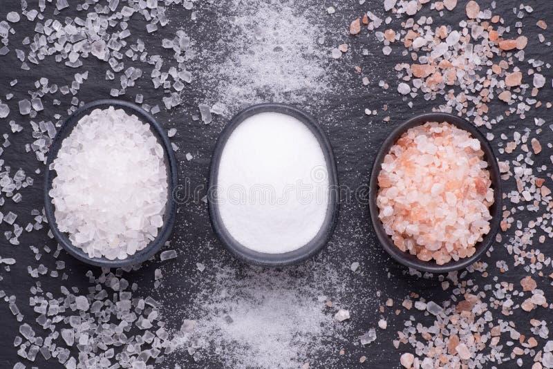 Divers genres de sel dans des cuvettes sur le fond en pierre noir photo libre de droits