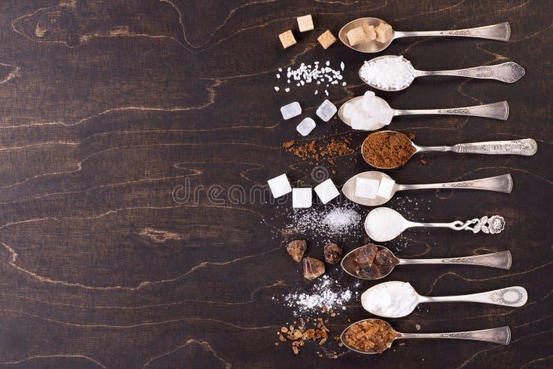 Divers genres de sucre dans de vieilles cuillères sur le fond en bois foncé image stock