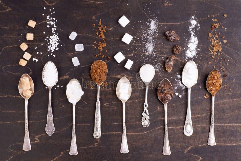 Divers genres de sucre dans de vieilles cuill?res sur le fond en bois fonc? photographie stock