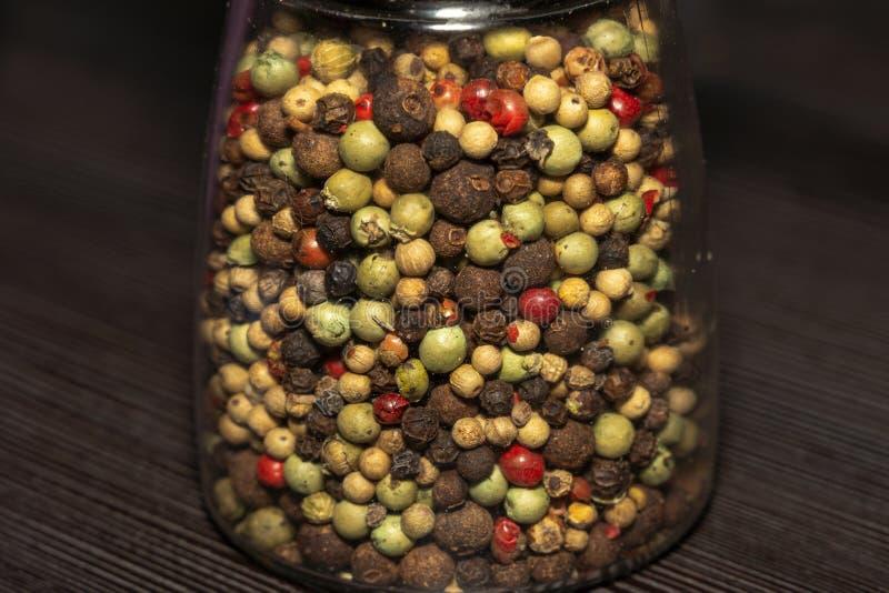 Divers grains de poivre mélangés dans un verre images stock