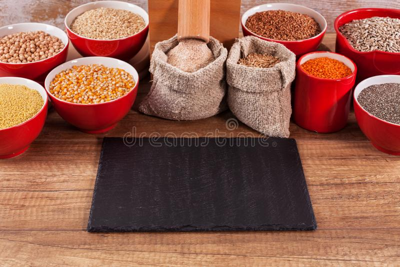 Divers grains et graines autour d'un moulin de table image libre de droits