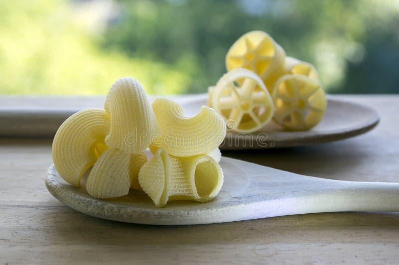 Divers mélange des pâtes sur deux cuillères en bois sur la table en bois, fond vert dehors photos stock