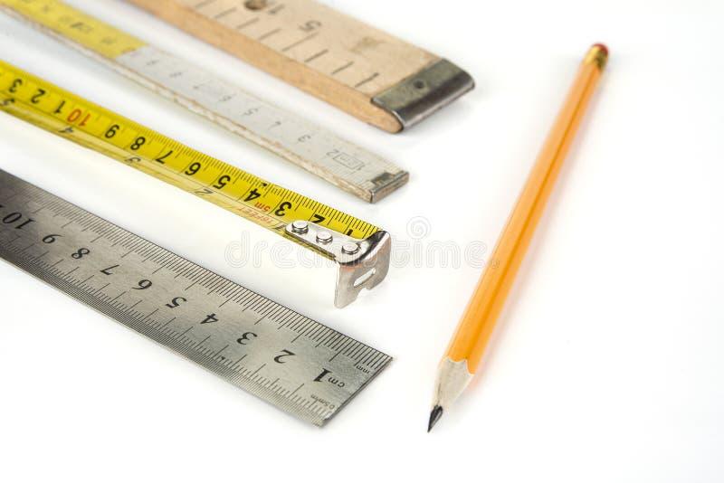 Divers m?tres sur un fond blanc avec le crayon image libre de droits