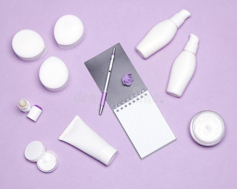 Divers produits cosmétiques avec le carnet et le stylo sur la table de femmes photographie stock
