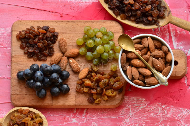 Divers raisins secs, baies de vigne et amandes sur le hachoir photo stock