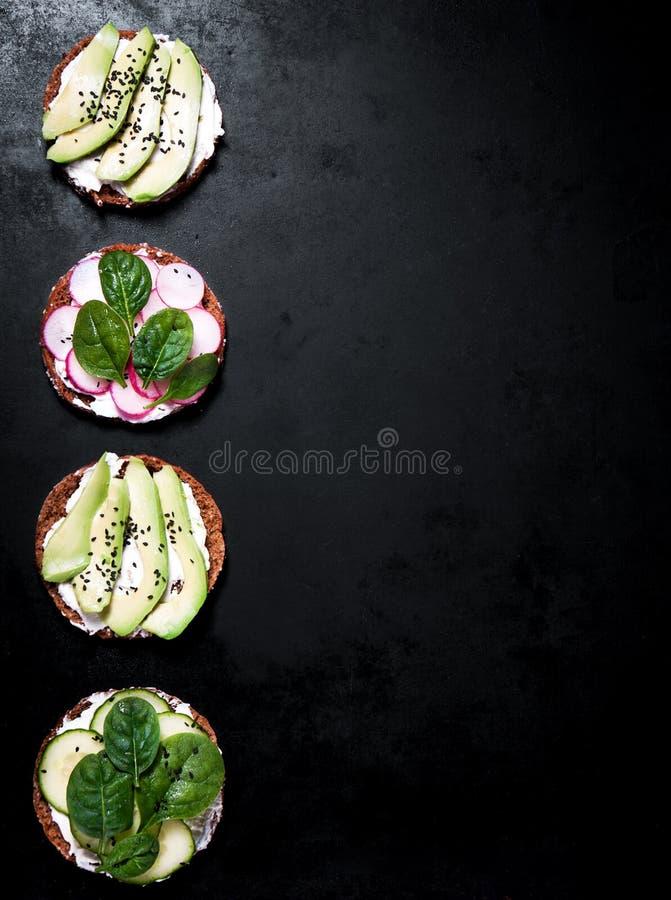 Divers sandwichs sains à végétarien ou à vegan avec différents légumes sur un fond foncé photos stock