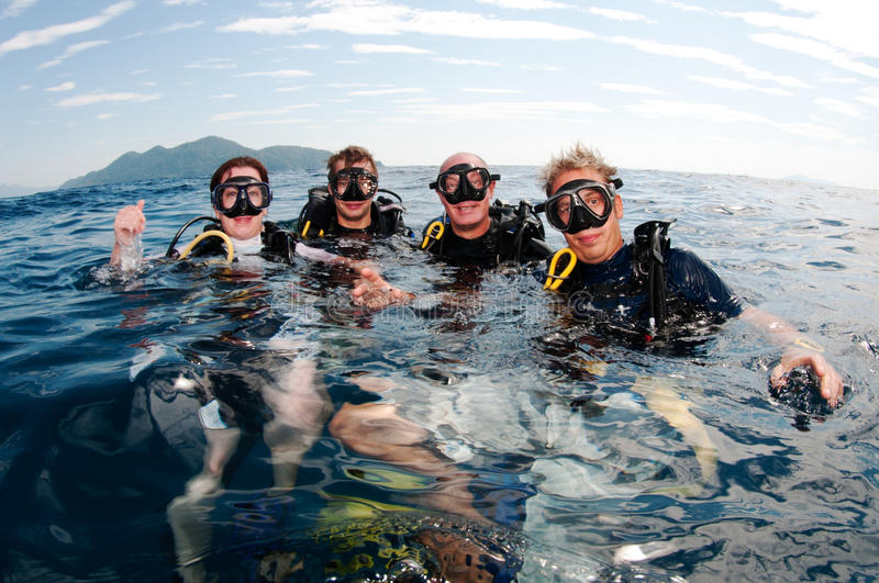 Divers scuba dive together on surface royalty free stock photos