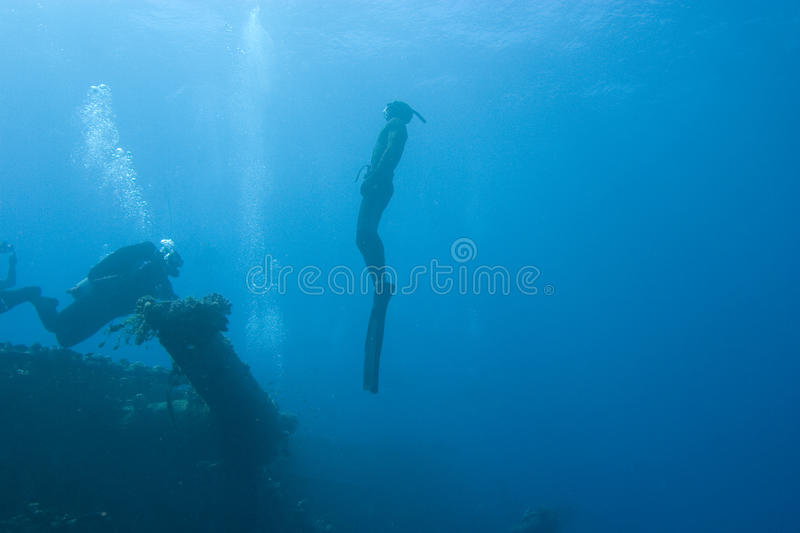 Divers and sunken ship stock images