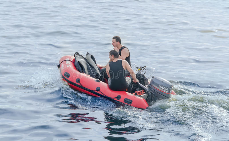 Divers training on the red rescue boat, trained soldiers. Aeronautic show.  stock photos