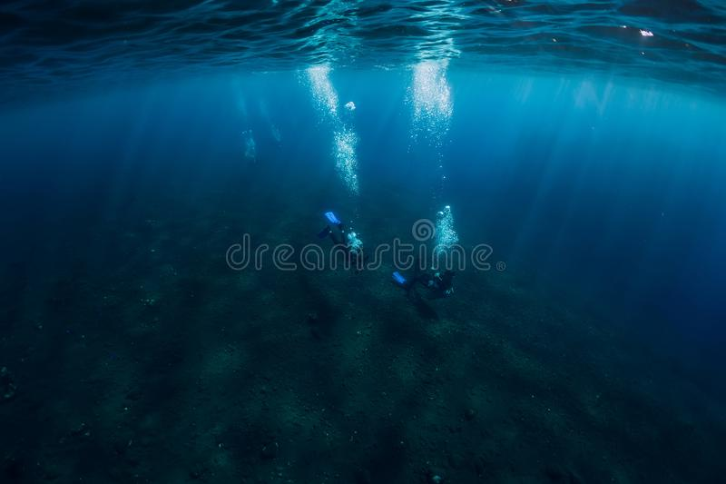 Divers underwater at shipwreck in Bali. Diving in sea royalty free stock photography