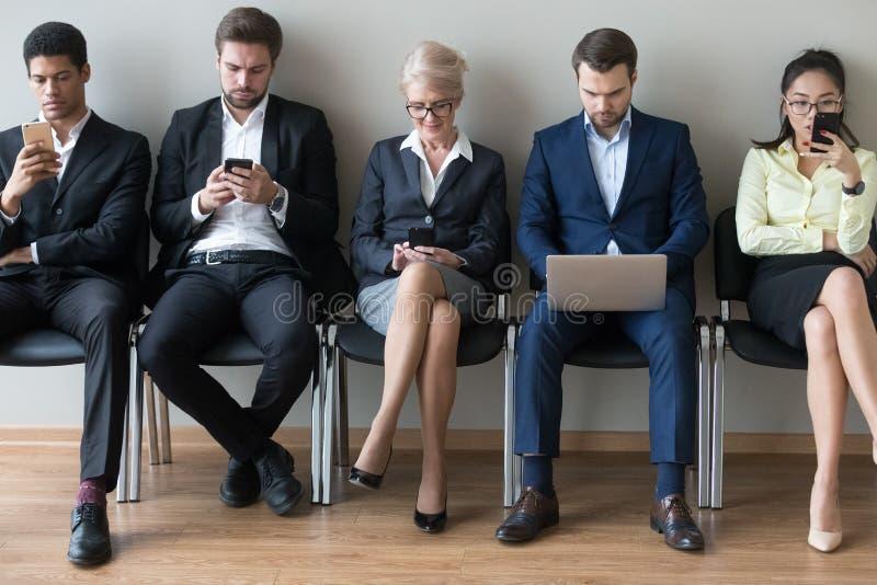 Divers zakenlui die in rij zitten die apparatentelefoons en laptop met behulp van royalty-vrije stock fotografie