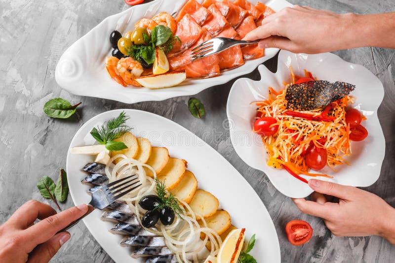 Diversa comida con el disco de los mariscos con la rebanada de la caballa ahumada, las patatas fritas, la ensalada de color salm imagen de archivo libre de regalías