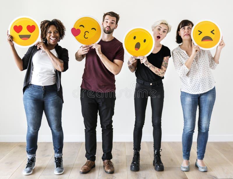 Diversa gente che tiene l'emoticon del fronte fotografie stock libere da diritti