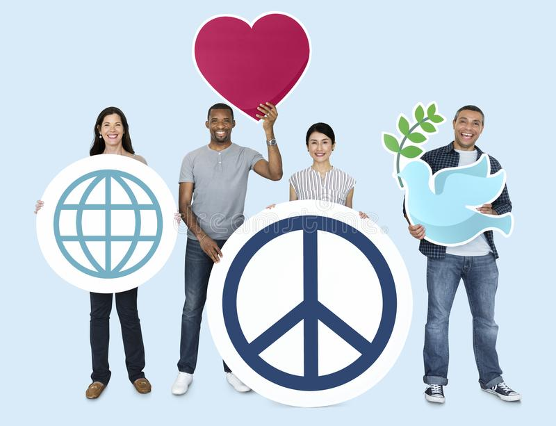 Diversa gente felice che tiene le icone di pace di mondo fotografie stock