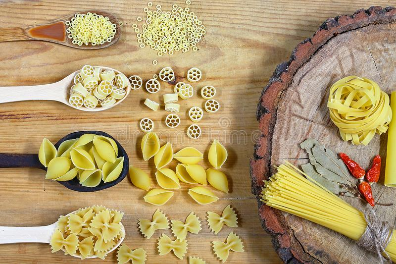 Diversa mezcla de pastas en fondo rústico de madera, las cucharas de madera, la pimienta roja de las especias, la hoja de laurel, imagen de archivo libre de regalías