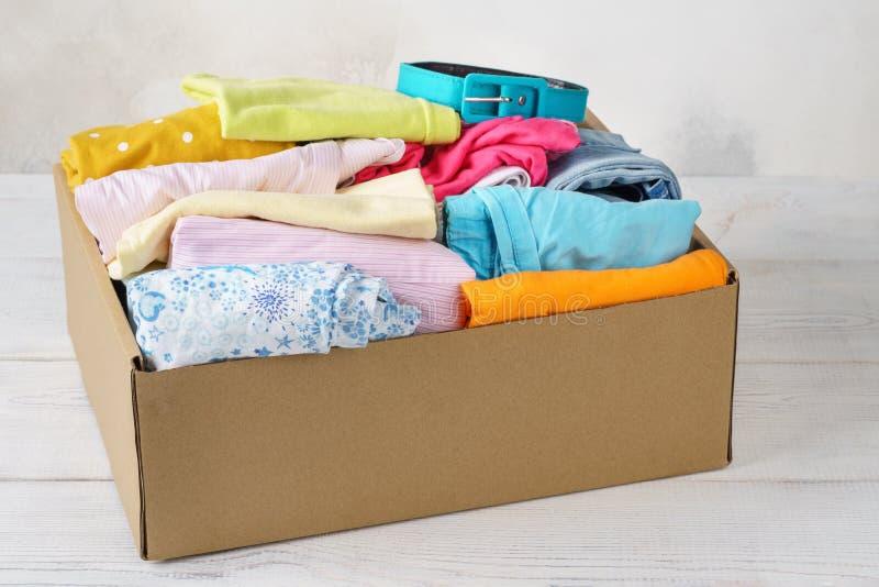 Diversa ropa colorida en una caja para enviar o la donación imagen de archivo