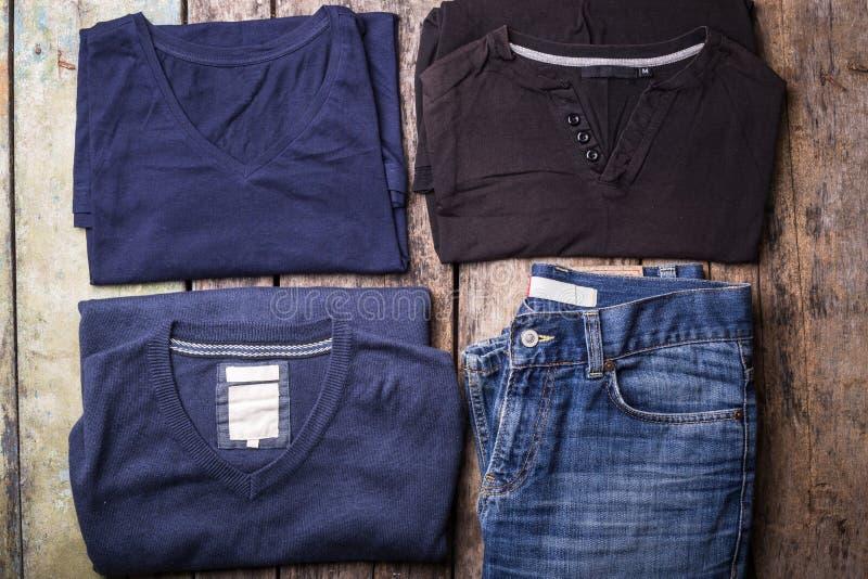 Diversa ropa del hombre recogida en fondo de madera imagen de archivo