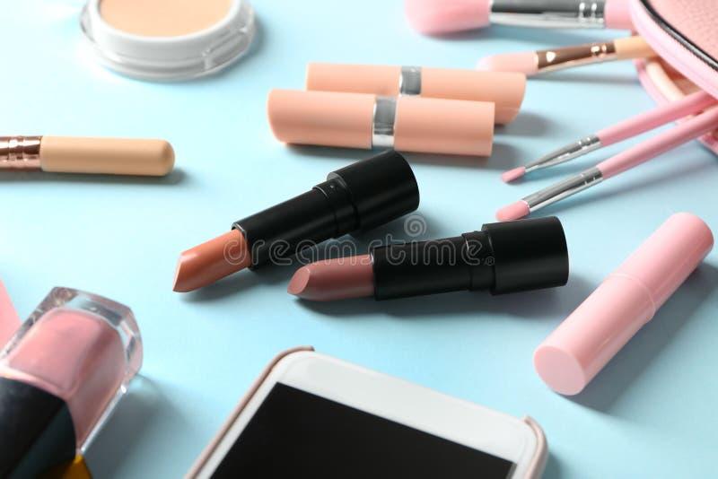 Diversas barras de labios y otros cosméticos en fondo del color fotografía de archivo