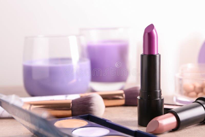 Diversas barras de labios y otros cosméticos en la tabla imágenes de archivo libres de regalías