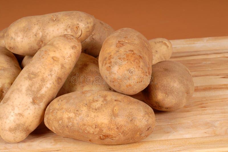 Diversas batatas de russet empilhadas em uma placa de estaca fotografia de stock royalty free