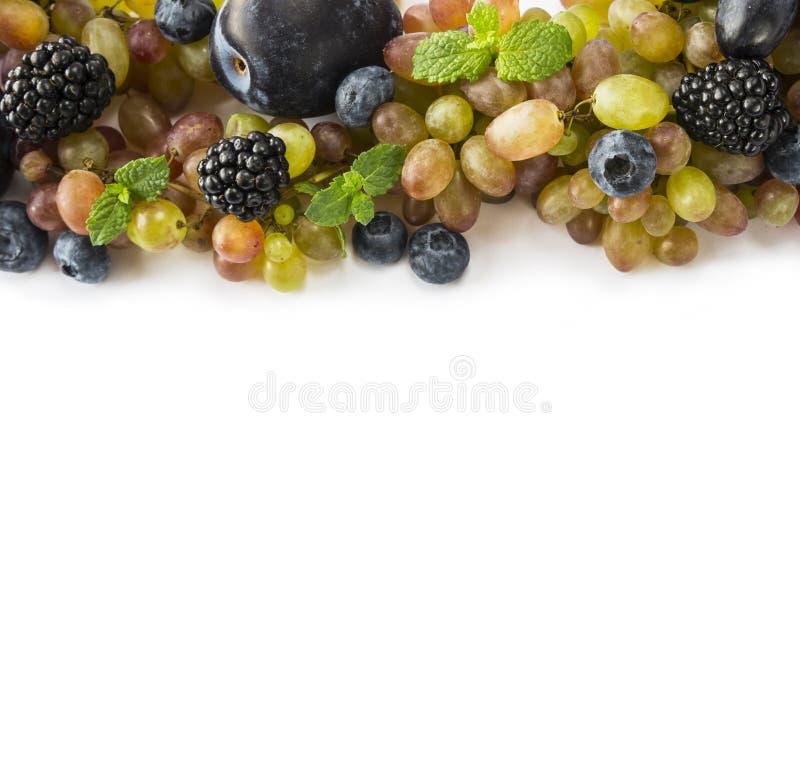 Diversas bayas y frutas frescas del verano en el fondo blanco Uva madura, arándanos, zarzamoras, ciruelos imagen de archivo libre de regalías