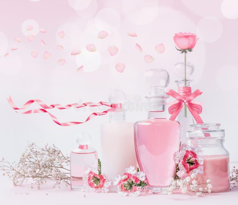 Diversas botellas de cristal cosméticas con las cintas rosadas y flores que se colocan en el fondo rosado blanco con el bokeh Cui imagen de archivo libre de regalías