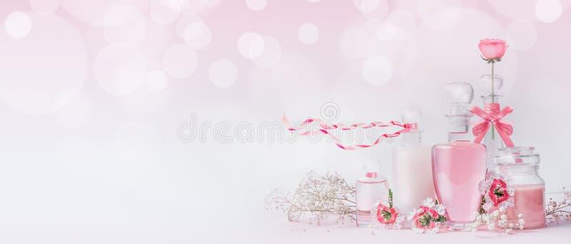 Diversas botellas de cristal cosméticas con las cintas rosadas y flores que se colocan en el fondo rosado blanco con el bokeh, la fotografía de archivo libre de regalías