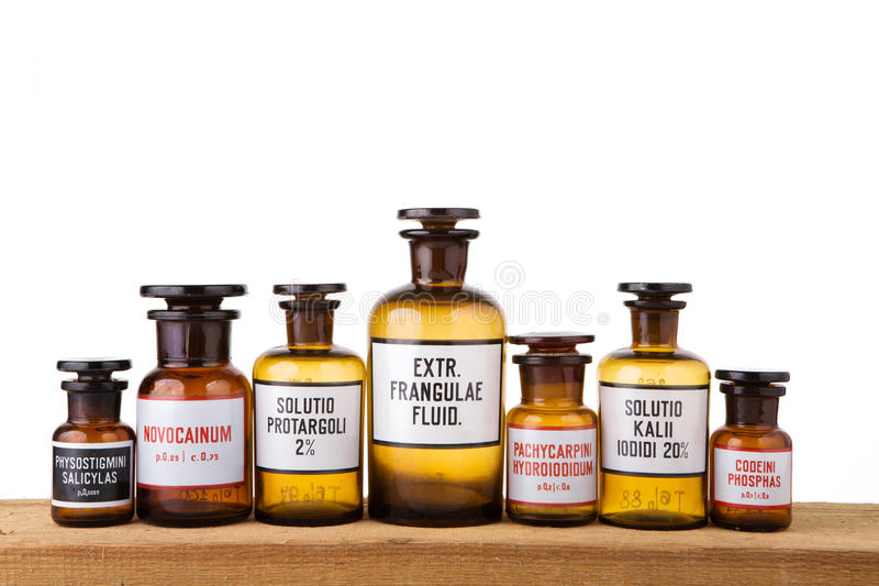 Diversas botellas de la farmacia del vintage en el tablero de madera imagenes de archivo