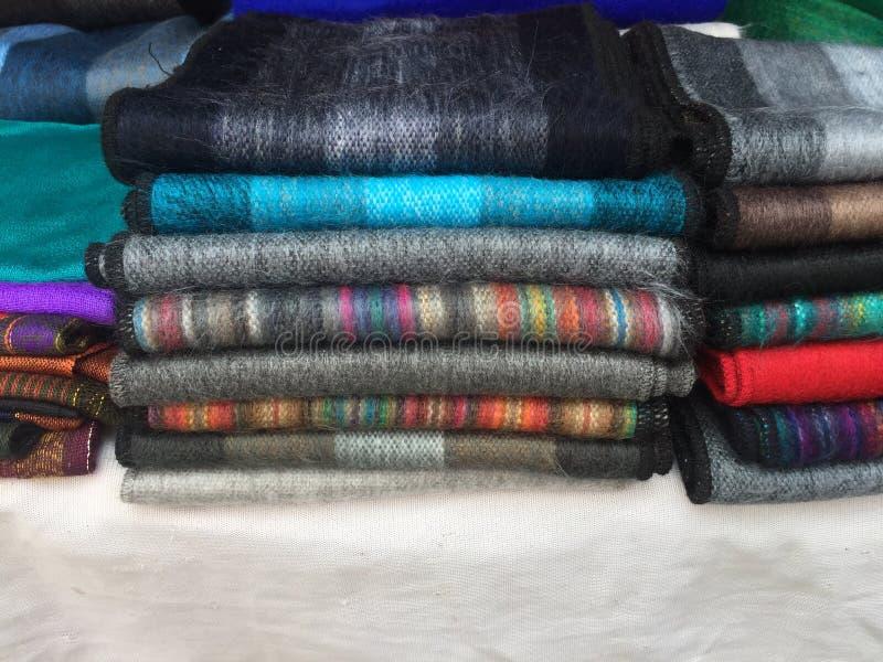 Diversas bufandas en varios colores y golpeteos andinos hicieron de lanas en venta en un soporte del mercado de Otavalo, Ecuador fotos de archivo