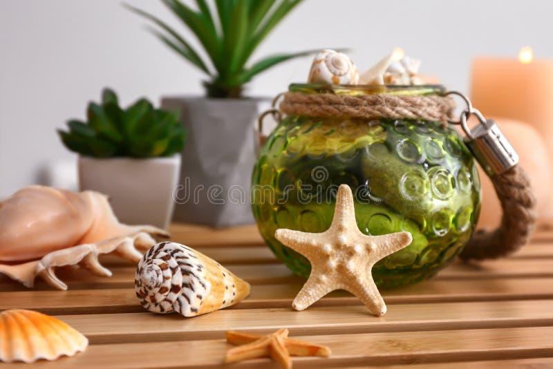 Diversas cáscaras del mar con las estrellas de mar en la tabla de madera fotografía de archivo
