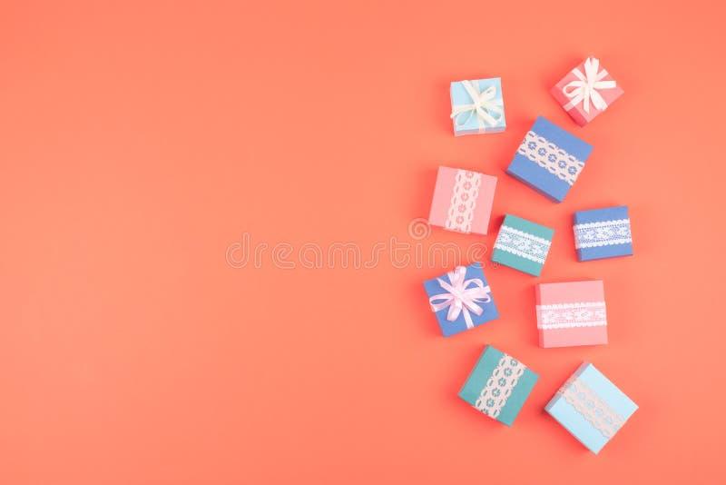 Diversas cajas de regalo de cumpleaños con el cordón en el fondo coralino del color Concepto m?nimo, endecha plana imágenes de archivo libres de regalías