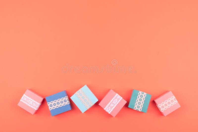 Diversas cajas de regalo de cumpleaños con el cordón en el fondo coralino del color Concepto m?nimo, endecha plana imagen de archivo