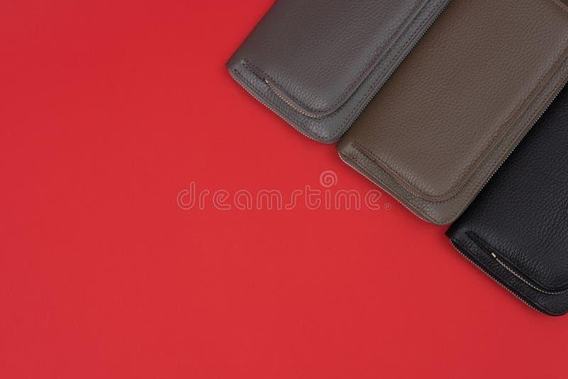 Diversas carteras de cuero en la cremallera Fondo rojo imagen de archivo
