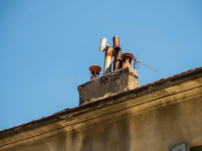 Diversas chimeneas de la diversión en el tejado tejado de la casa en la ciudad de Edessa, Grecia imagenes de archivo