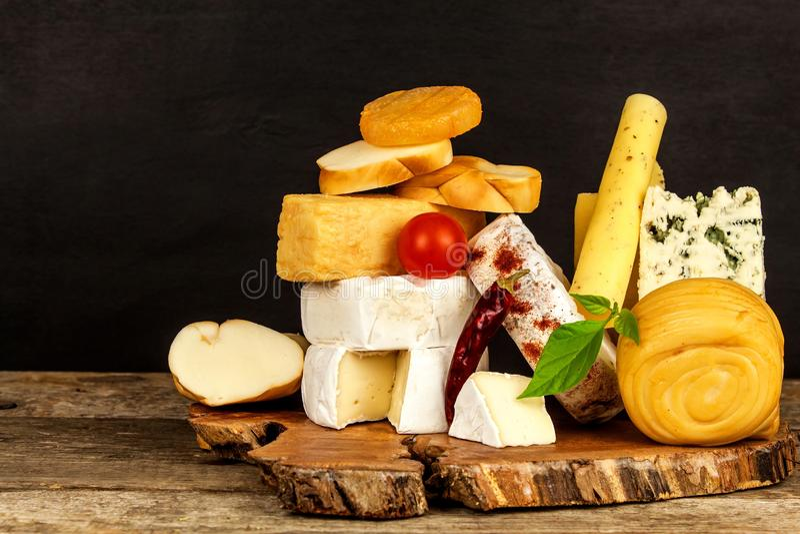 Diversas clases de queso servidas en la tabla de madera Tablero de madera con los diferentes tipos de queso delicioso en la tabla imágenes de archivo libres de regalías