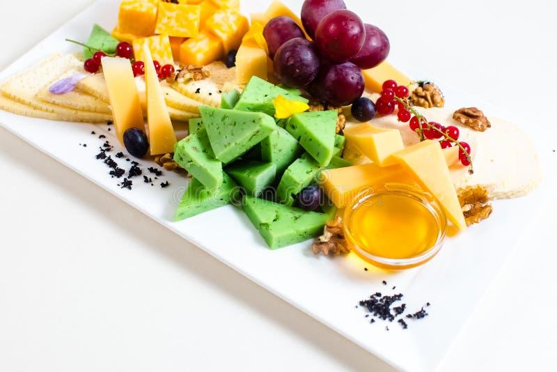 Diversas clases de queso, uvas cortadas, rojas, nueces, miel en un cuenco, pasa roja, queso verde, soporte de madera foto de archivo