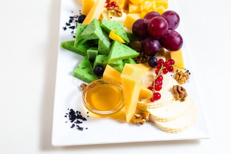 Diversas clases de queso, uvas cortadas, rojas, nueces, miel en un cuenco, pasa roja, queso verde, soporte de madera imagen de archivo