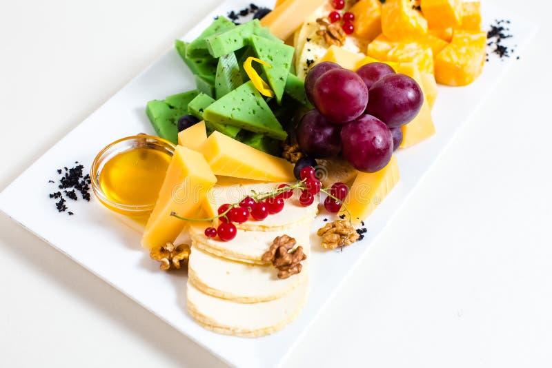 Diversas clases de queso, uvas cortadas, rojas, nueces, miel en un cuenco, pasa roja, queso verde, soporte de madera imagen de archivo libre de regalías