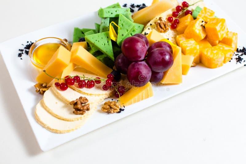 Diversas clases de queso, uvas cortadas, rojas, nueces, miel en un cuenco, pasa roja, queso verde, soporte de madera fotografía de archivo