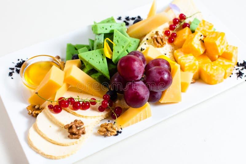 Diversas clases de queso, uvas cortadas, rojas, nueces, miel en un cuenco, pasa roja, queso verde, soporte de madera imagenes de archivo