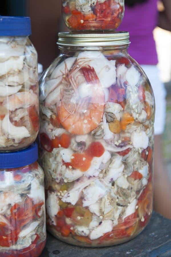 Diversas comidas en el vinagre - mariscos en las botellas de cristal para la venta en una parada del mercado foto de archivo libre de regalías