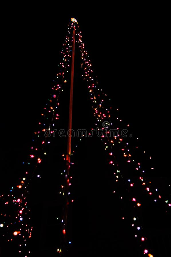 Diversas cores das luzes obscuras decoradas por todo o lado em uma árvore de Natal fotografia de stock royalty free