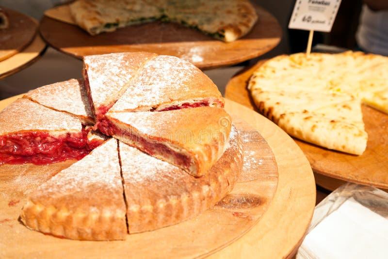 Diversas empanadas cortadas en el mercado de la comida Pedazos de empanada cortada en pedazos de la fruta imagenes de archivo