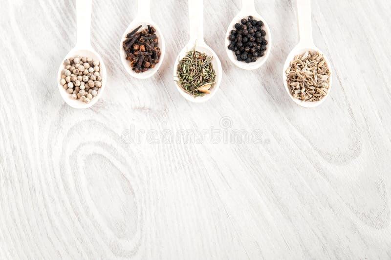 Diversas especias e hierbas en cucharas de madera en el fondo blanco de la tabla Pimienta blanco y negro, cl imagen de archivo libre de regalías