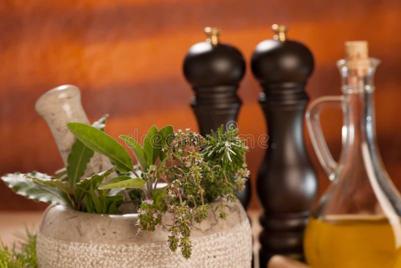 Diversas especias en una tabla de madera con el mortero, la maja y los molinos fotos de archivo libres de regalías