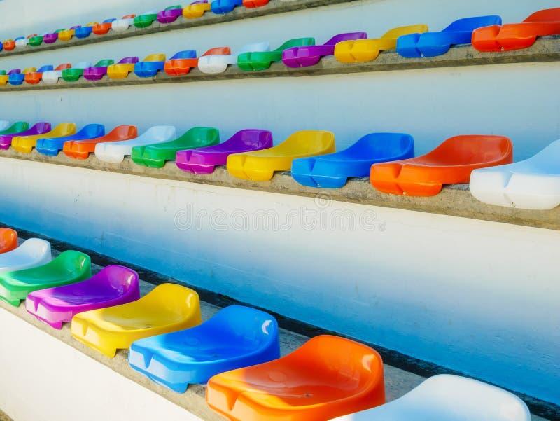 Diversas fileiras de assentos coloridos em um stadion fotografia de stock