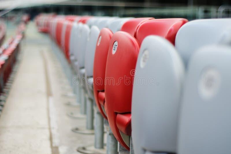 Diversas fileiras de assentos vermelhos e brancos do estádio imagem de stock
