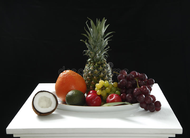 Diversas frutas frescas del coco, de la piña, de maduro, manzanas y uva en la tabla blanca en el fondo negro para sano foto de archivo