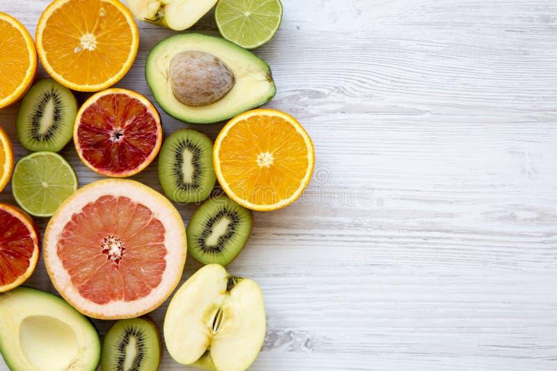 Diversas frutas frescas en la superficie de madera blanca con el espacio de la copia, visión superior imágenes de archivo libres de regalías